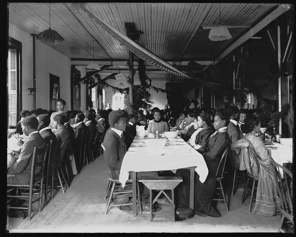Interior view of dining hall, decorated for the holidays, with students sitting at tables at the Tuskegee Institute