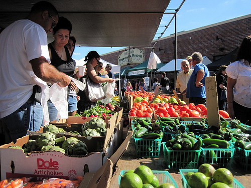 Consumers shop for local produce at the Winter Park farmers market in Winter Park, FL.