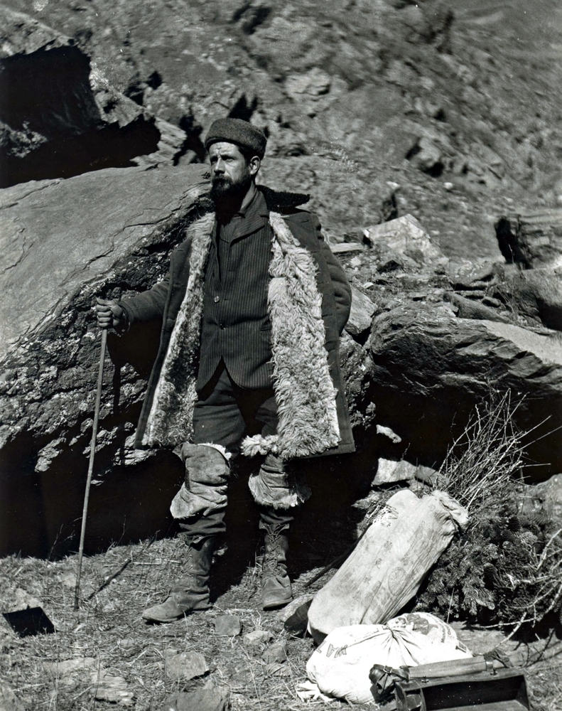 Meyer standing on mountainous terrain, dressed in winter gear and holding a walking stick.