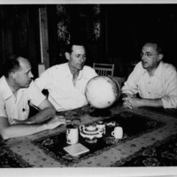 Photograph of Edward F. Knipling and researchers seated at table with globe