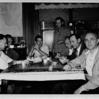 Photograph of Edward F. Knipling and his staff at dining table with map of Sanibel in background