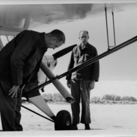 Photograph of researchers inspecting airplane chute for fly release