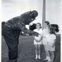 Smokey Bear greets three youthful fans in Washington, D.C.