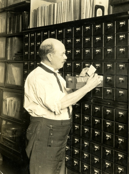 Photograph of Albert Hassal going through the drawer of a card catalog.