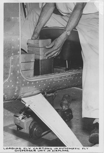 "Thumbnail for the first (or only) page of Photograph ""Loading Fly Cartons in Automatic Fly Dispenser Unit in Airplane."
