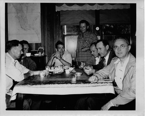 Thumbnail for the first (or only) page of Photograph of Edward F. Knipling and his staff at dining table with map of Sanibel in background.