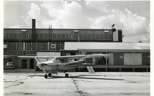 Thumbnail for the first (or only) page of Dispersing plane parked in front of loading platform of box assembly building.