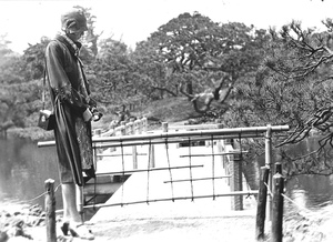 Thumbnail for the first (or only) page of Meditating at a bamboo gate barrier to a bridge across a portion of a small lake in Oushi Park. 4/28/1929. Photograph #43466..