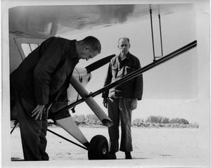 Thumbnail for the first (or only) page of Photograph of researchers inspecting airplane chute for fly release.