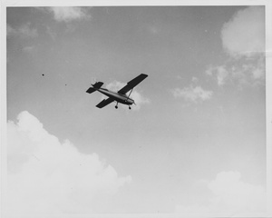 Thumbnail for the first (or only) page of Photograph of plane releasing boxes.