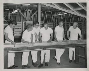 Thumbnail for the first (or only) page of Edward F. Knipling and colleagues inspecting pupae trays at Mission, Texas plant. Knipling fourth from left..