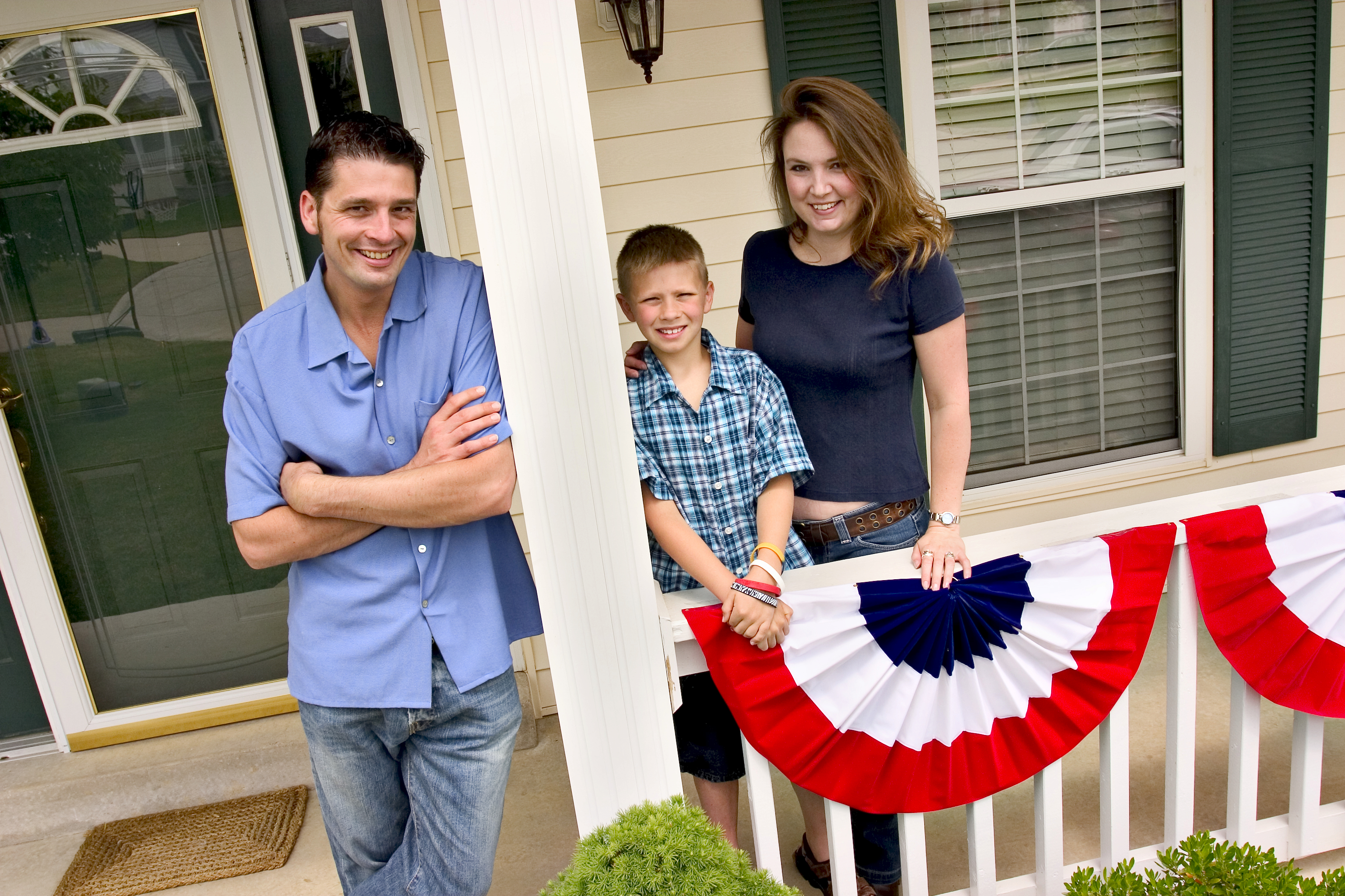 Family standing on front porch of house: Copyright iStock Photos