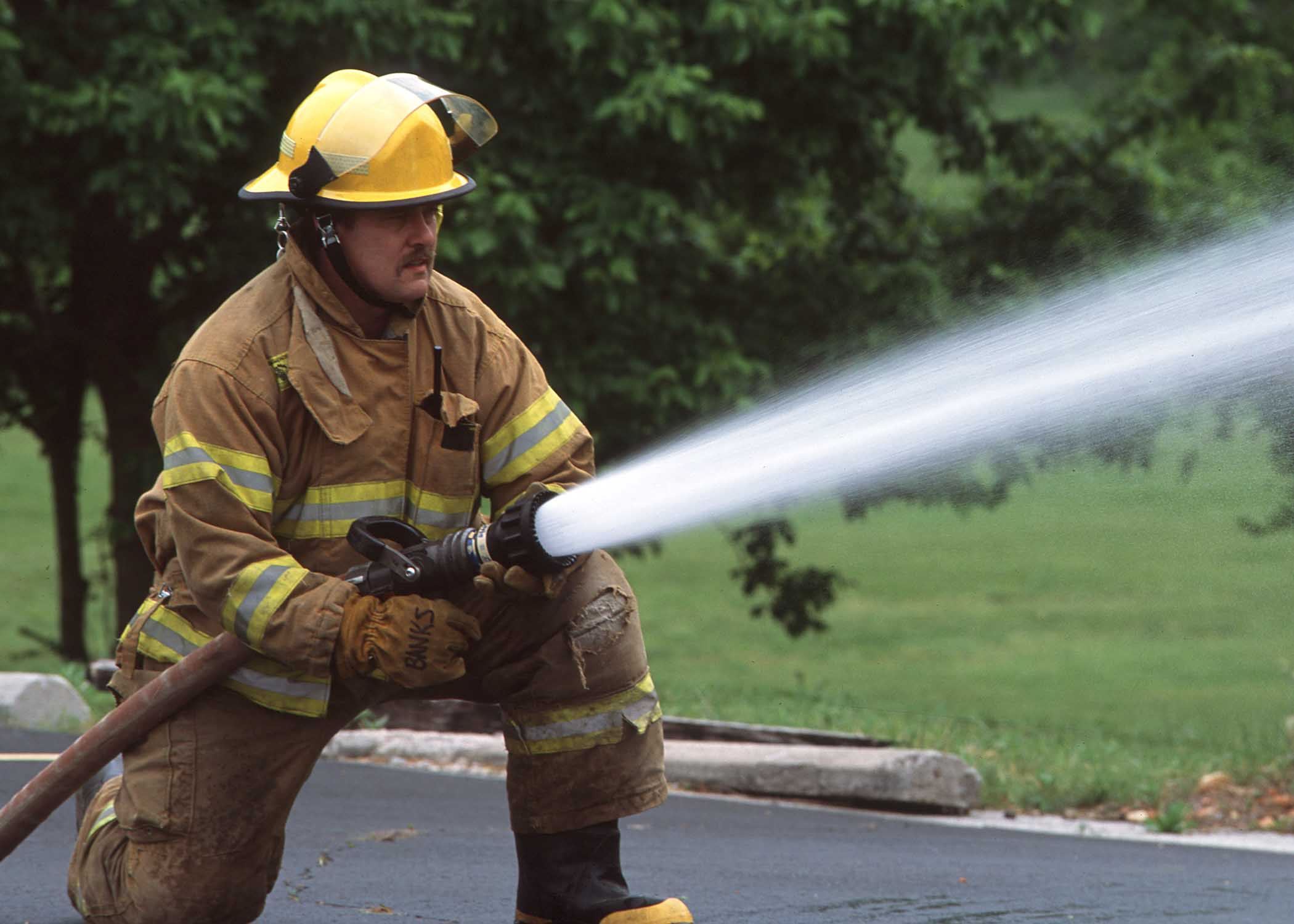 Fireman holding a firehose shooting water. (NRCS|USDA)