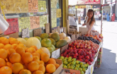 Woman shopping at an international, outdoor vegetable stand.  (Copyright IStock)