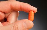 a hand holding a pill