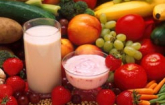Display of healthy fruits, vegetables and a glass of milk and cup of yogurt