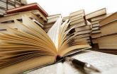 stacks of books on a table - one open: Copyright iStock Photos