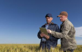 Farmers looking at a laptop (Copyright IStock).