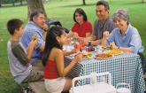 people of all ages sitting at outdoor picnic table