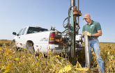 U.S. Department of Agriculture Agriculture Research Service technician prepares a large core sampler to take a core sample of the wood chip bioreactor beneath a soybean field for lab analysis of denitrification rates and bacterial populations