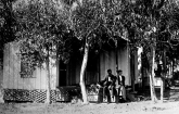 Two workers rest on the porch of a small house surrounded by trees.