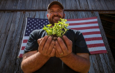 U.S. Marine Corps veteran Calvin Riggleman holds an oregano seedling and soil on Bigg Riggs farm in Hampshire County, WV on Wednesday, Jun. 24, 2015.