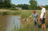 NRCS District Conservationist points out minnows swimming in a pond