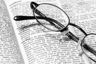A pair of eyeglasses sitting on a book. (Copyright IStock)