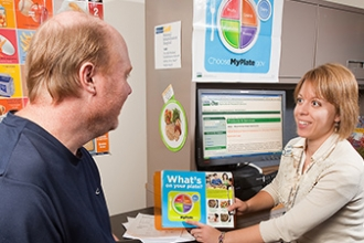 Clinical dietitian Berit Christensen (right) uses materials from ChooseMyPlate.gov and the U.S. Department of Agriculture (USDA) Agriculture Research Service (ARS) National Nutrient Database to teach a recovering stroke patient how to manage weight and bl