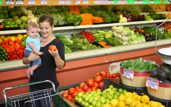 Young mother with baby selects items in produce aisle of grocery store