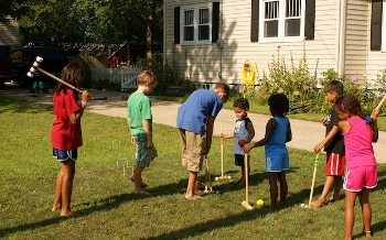 Children paying croquet on lawn