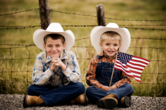 Two boys in cowboy hats sitting on country road with U.S. flag. (iStock)