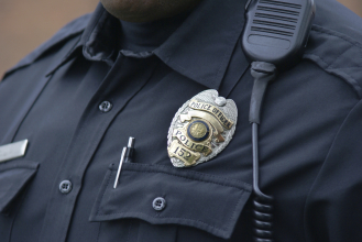 police in uniform showing badge: Copyright iStock Photo