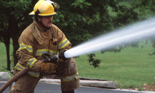 Fireman holding a fire hose shooting water: USDA/NRCS